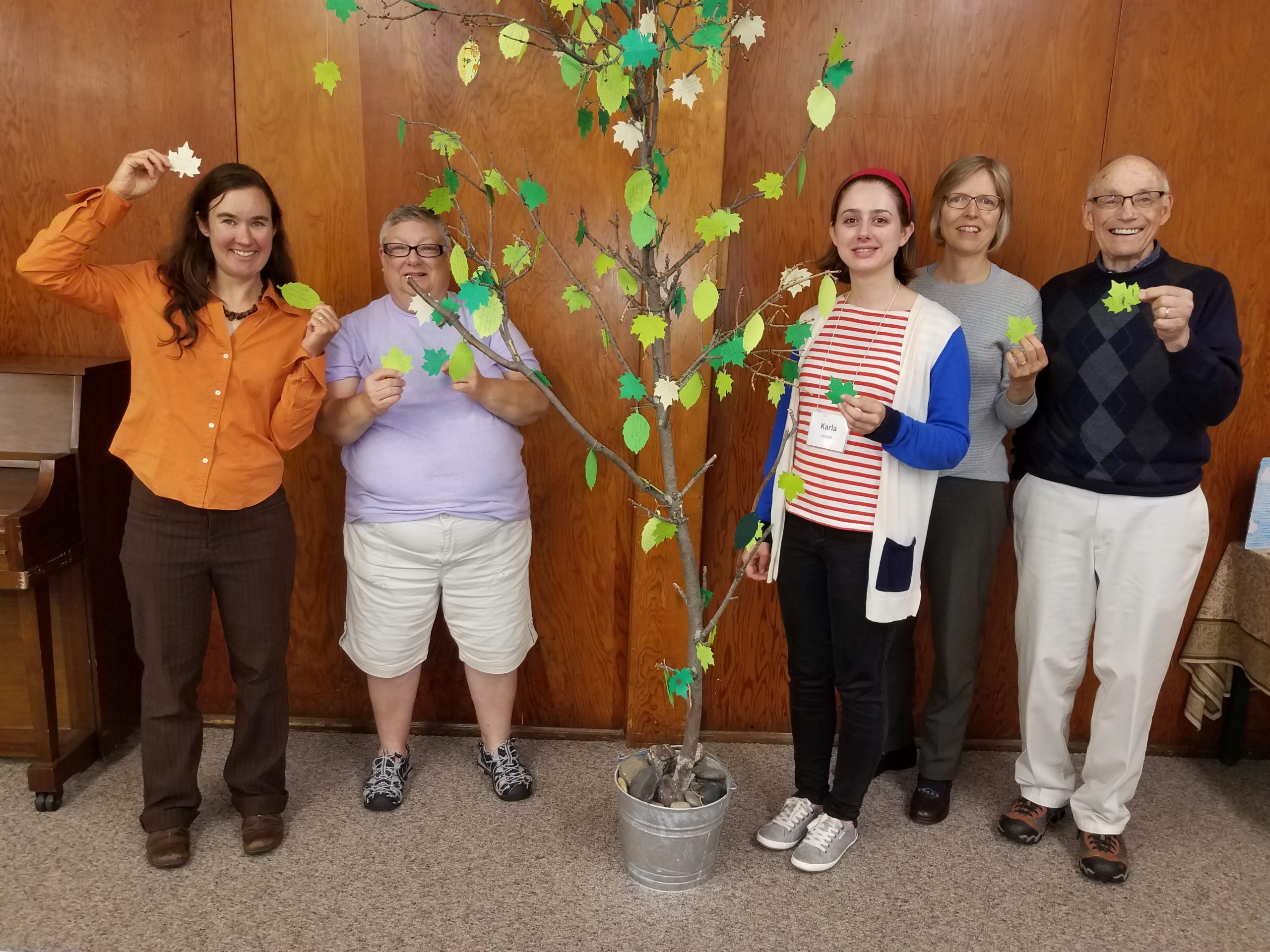 Members of the Eco-Justice Committee smile and hold paper leaves with creation care actions written on them.