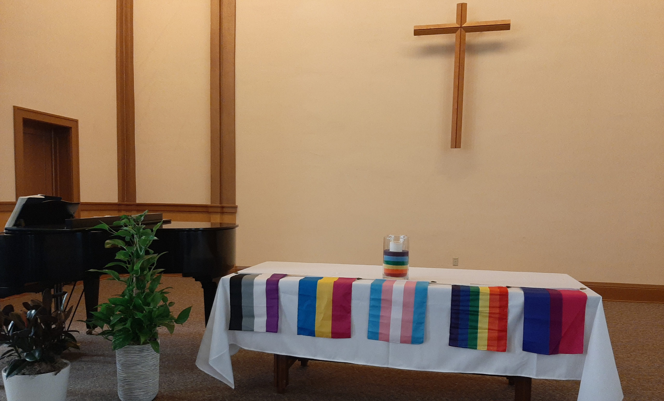 Various pride flags are displayed in the sanctuary of Faith Mennonite Church.
